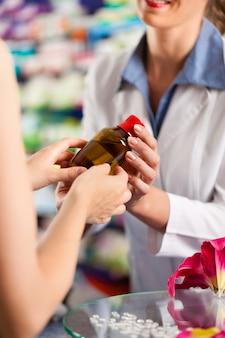 Pharmacienne dans sa pharmacie avec un client