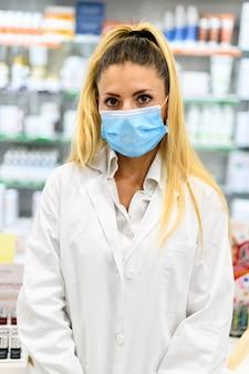 Pharmacienne avec masque de protection sur son visage travaillant à la pharmacie. concept de soins médicaux.