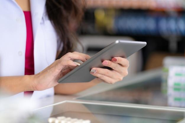 Une pharmacienne utilise une tablette numérique à la pharmacie