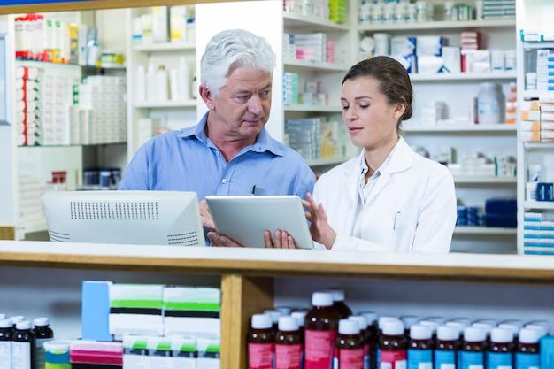 Pharmaciens à l'aide de tablette numérique au comptoir