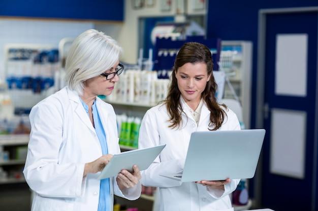 Pharmaciens à l'aide d'une tablette numérique et d'un ordinateur portable