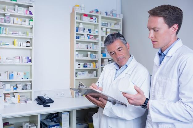 Pharmaciens détenant des médicaments et écrivant une ordonnance à la pharmacie