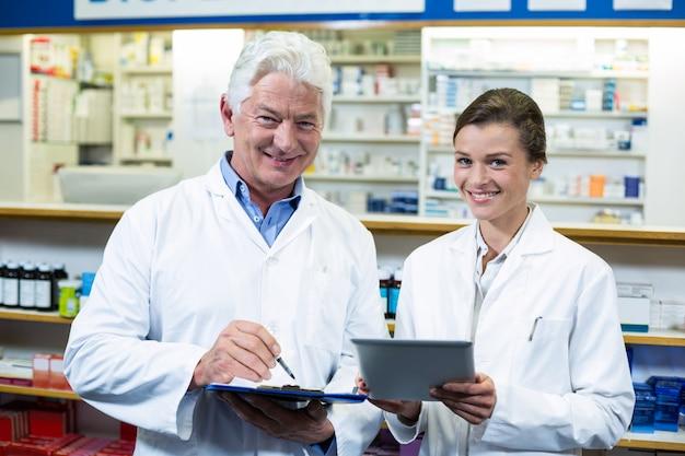Pharmaciens discutant sur tablette numérique et presse-papiers en pharmacie