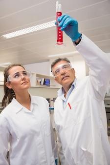 Pharmaciens regardant bécher de liquide rouge