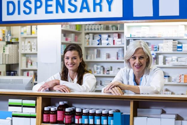 Pharmaciens souriants debout au comptoir en pharmacie