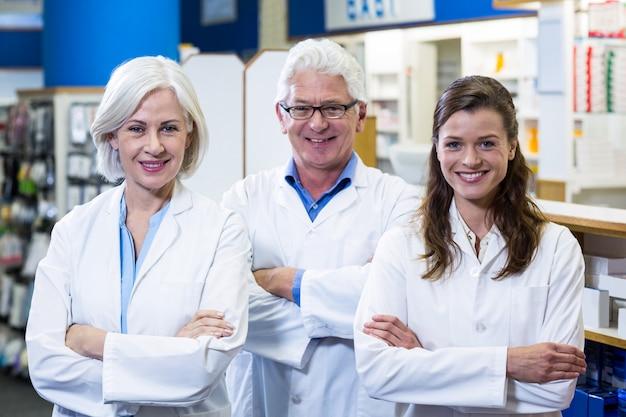 Pharmaciens souriants debout avec les bras croisés en pharmacie