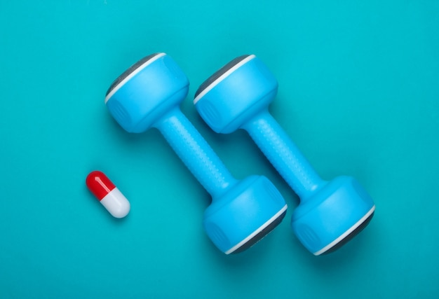 Pharmacologie dans le sport. haltère et capsule sur fond bleu. vitamines, stéroïdes. vue de dessus