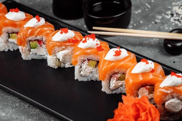 Philadelphia roll sushi au saumon, anguille fumée, concombre, avocat, fromage à la crème, caviar rouge. carte de sushis. nourriture japonaise