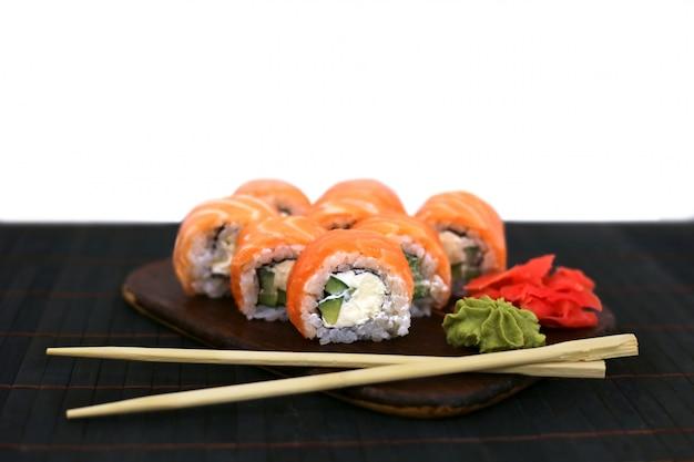 Philadelphia roule avec du saumon sur table noire à côté de baguettes. concept de cuisine japonaise