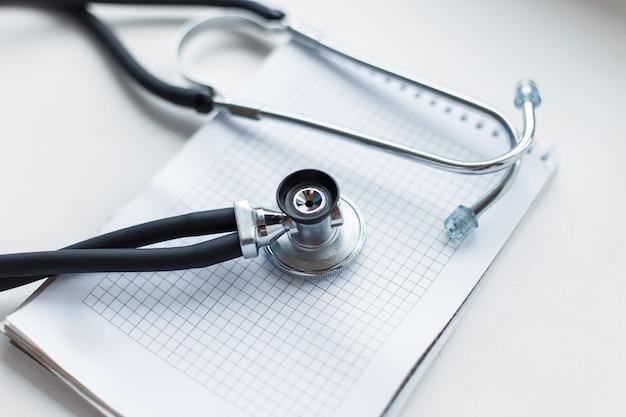 Phonendoscope médical avec un ordinateur portable sur fond blanc.