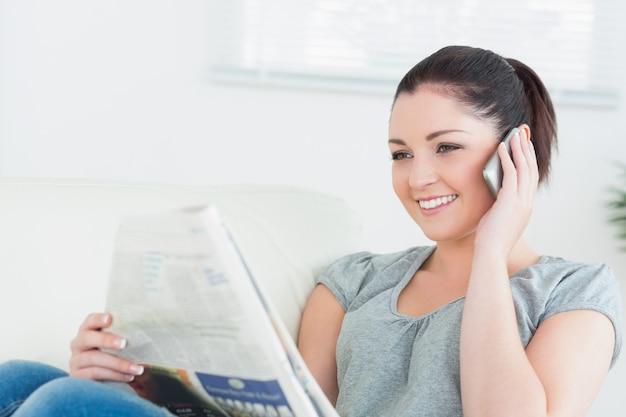 Phoning femme lisant le journal sur le divan