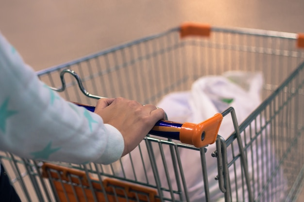 Photo abstraite d'une femme qui roule un chariot ou un chariot dans un supermarché avec un arrière-plan flou