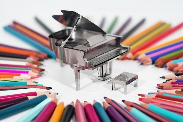 Photo abstraite de la musique. petit piano en métal avec carnet de notes.