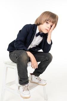 Photo d'un adolescent en costume noir et baskets blanches est assis sur ses genoux et pas heureux isolé