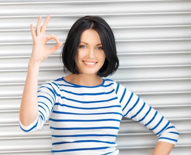 Photo d'une adolescente heureuse montrant un signe ok