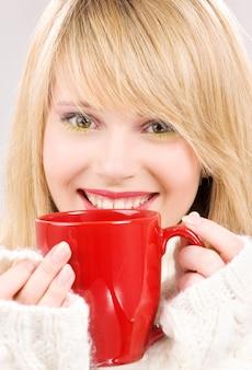 Photo d'une adolescente heureuse avec une tasse rouge