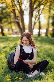 Photo d'une adolescente positive et joyeuse passe du temps dans le parc et utilise un téléphone portable.