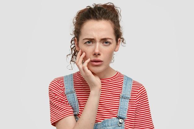 Photo d'une adolescente sérieuse fronce les sourcils face au mécontentement, garde la main sur la joue