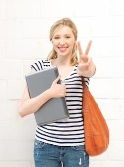 Photo d'une adolescente souriante avec un ordinateur portable montrant le signe de la victoire