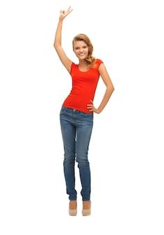 Photo d'une adolescente en t-shirt rouge montrant le signe de la victoire