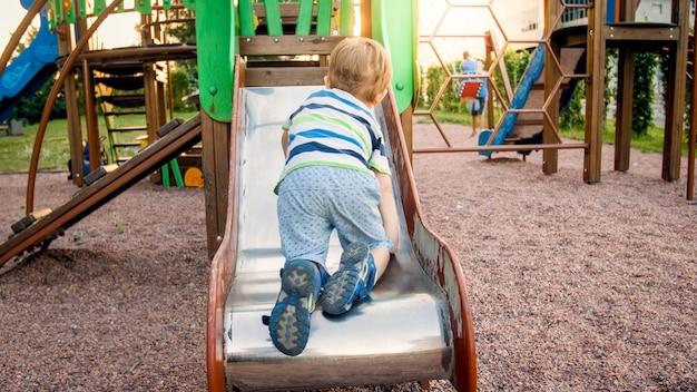 Photo d'un adorable garçon souriant qui grimpe et monte sur un toboggan. enfant actif s'amusant et jouant au parc