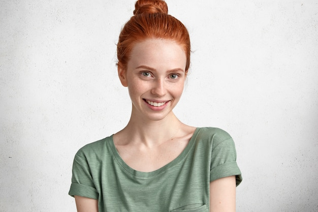 Photo d'adorable jeune femme aux taches de rousseur satisfaits aux cheveux roux attachés en noeud, sourit agréablement à la caméra, se réjouit des vacances à venir, isolé sur blanc