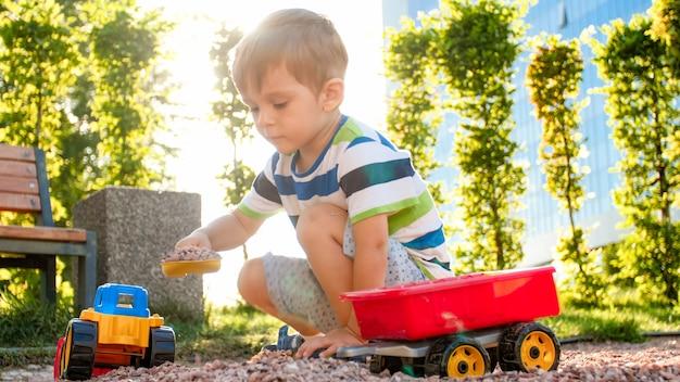 Photo d'un adorable petit garçon de 3 ans jouant avec du sable et vous camion et remorque dans le parc. enfant creusant et construisant dans le bac à sable