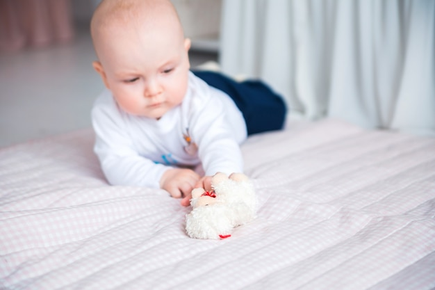 Photo d'adorable petit garçon allongé sur le sol dans sa chambre d'enfant et jouer avec des jouets