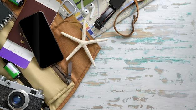Photo aérienne des accessoires du voyageur avec smartphone, appareil photo, carte d'embarquement et autres articles de voyage
