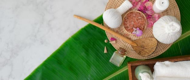 Photo aérienne d'accessoires de spa avec une serviette blanche, de l'huile aromatique, du sel de spa et un espace de copie
