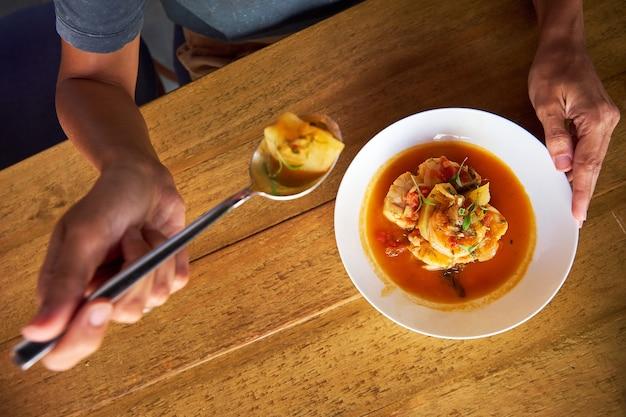 Photo aérienne d'une casserole avec de la morue et des crevettes avec des pommes de terre et de l'aïoli au poivre de palme pendant qu'une personne la mange avec une cuillère dans une table en bois