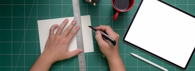 Photo aérienne de coupe papier étudiant avec cutter sur tapis de découpe