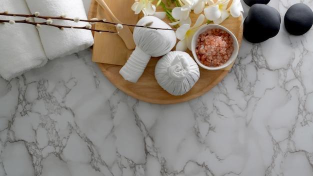 Photo aérienne du concept de traitement et de relaxation avec une serviette blanche, du sel de spa, des pierres chaudes et d'autres accessoires de spa