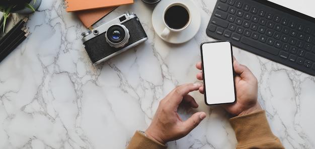 Photo aérienne du photographe professionnel tenant un smartphone avec un écran blanc dans un style