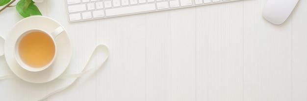 Photo aérienne d'un espace de travail avec une tasse de thé, un ordinateur et un espace de copie sur une table à planches