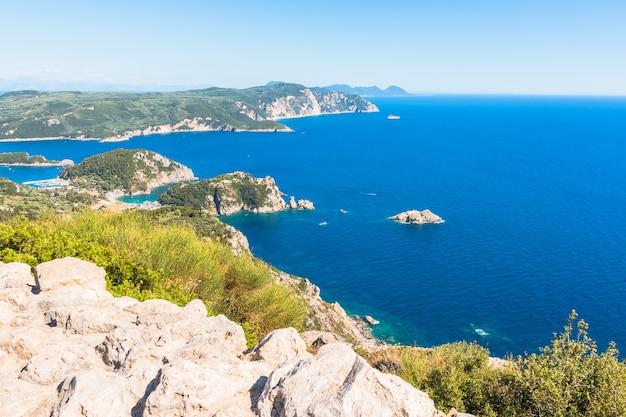 Photo aérienne d'une falaise, d'un golfe, d'une mer aux eaux cristallines et de bateaux. paysage de vue de dessus depuis un sommet de montagne. voyage paradisiaque pour un couple en quête d'aventure.