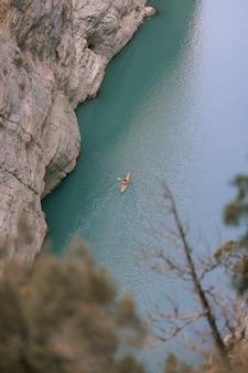 Photo aérienne d'un kayak dans une rivière entre les montagnes