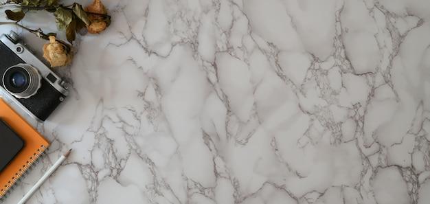 Photo aérienne d'un lieu de travail branché avec copie espace, appareil photo et fournitures de bureau sur table en marbre