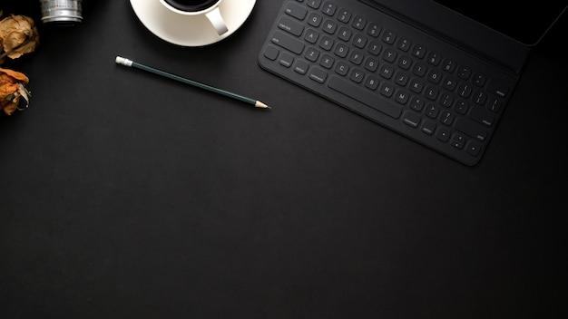 Photo aérienne d'un lieu de travail moderne sombre avec clavier sans fil, espace copie, appareil photo et tasse de café sur le tableau noir