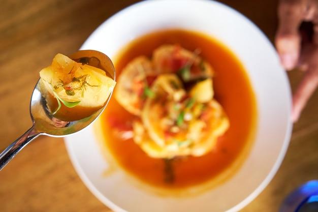 Photo aérienne avec la mise au point sélective sur une cuillère avec un morceau de pomme de terre d'une casserole avec de la morue et des crevettes avec des pommes de terre et de l'aïoli au poivre de palme dans une table en bois