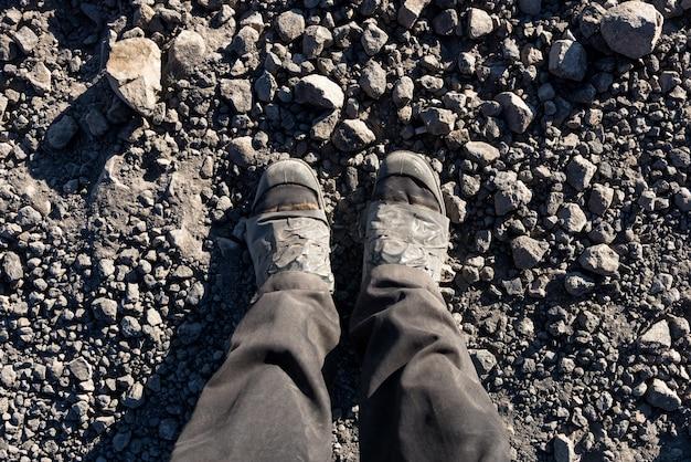 Photo aérienne de pieds sur un fond de sol brun. pieds d'homme