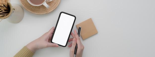 Photo aérienne d'un pigiste à l'aide d'une maquette de smartphone pour contacter le client