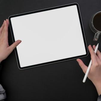 Photo aérienne d'un pigiste travaillant sur une tablette à écran vide dans un espace de travail moderne sombre