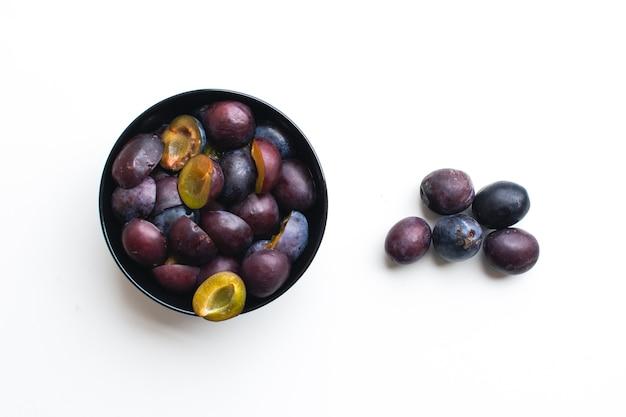 Photo aérienne de prunes organiques fraîches sur fond blanc