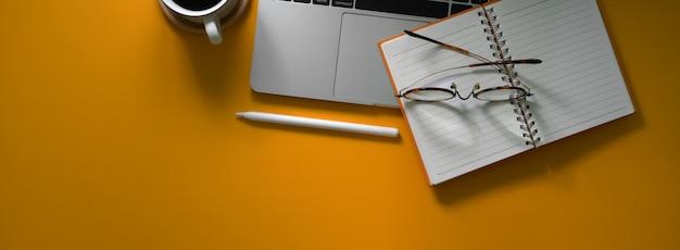 Photo aérienne d'une table de travail créative avec ordinateur portable, cahier vierge, fournitures et espace de copie