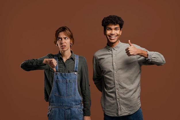 Photo d'agriculteurs couple mignon. une agricultrice montre le pouce vers le bas mais un homme se présente. femme porte une salopette en denim, l'homme porte un t-shirt, fond de couleur marron isolé.