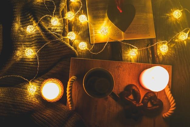 Photo d'ambiance de vacances. lumières de noël et pull en tricot chaud. tasse à thé chaud avec un livre pour une soirée confortable. pain d'épice sucré et coeur en bois sur plateau. plat d'hiver parfait avec bougie. concept hygge