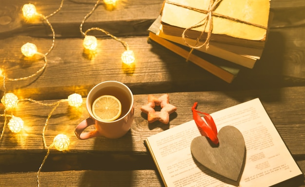 Photo d'ambiance de vacances. lumières de noël et tasse de thé chaud. réservez pour une soirée cosy. pain d'épice sucré et coeur en bois sur plateau. pose à plat d'hiver parfaite. concept d'hygiène.