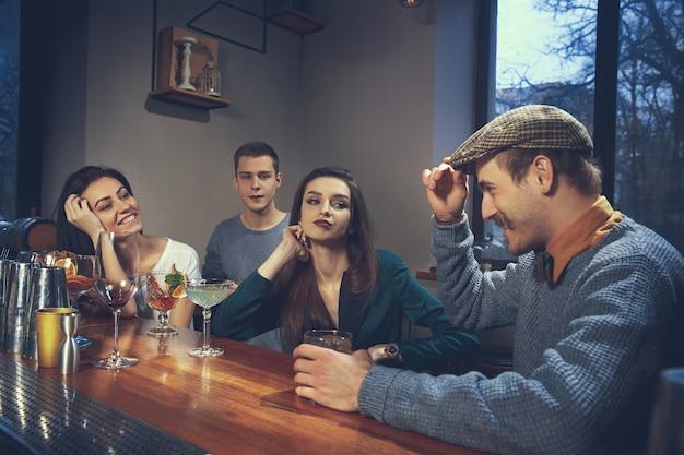 Photo d'amis joyeux dans le bar ou au pub communiquant entre eux