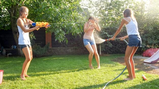 Photo amusante d'une famille heureuse avec des enfants jouant et éclaboussant de l'eau avec des pistolets à eau et un tuyau d'arrosage lors d'une chaude journée ensoleillée